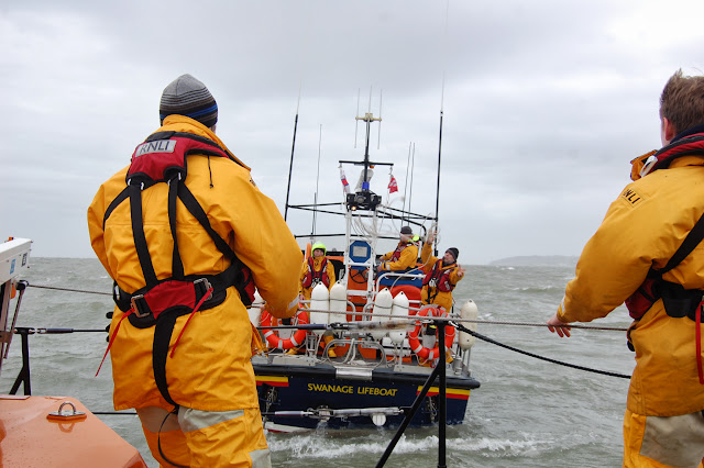 Swanage lifeboat crew member throws the heaving line attached to a tow rope during a training exercise with Poole all-weather lifeboat in Poole Bay on Sunday 23 February 2014. Photo: RNLI/Dave Riley