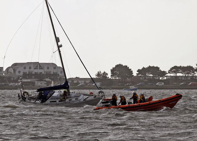 The ILB manoeuvres close to the yacht and the crew attempt to catch the mast halyard - 27 October 2013.  Photo credit: Mike Millard