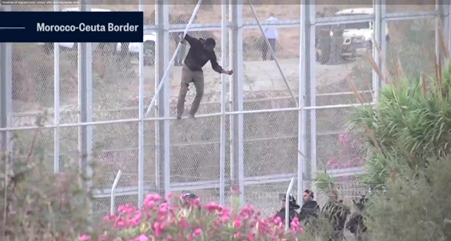 Screenshot from a video showing migrants storming border fences separating Spain's North African enclave of Ceuta from Morocco to get into Europe, on 26 July 2018. Photo: NBC News