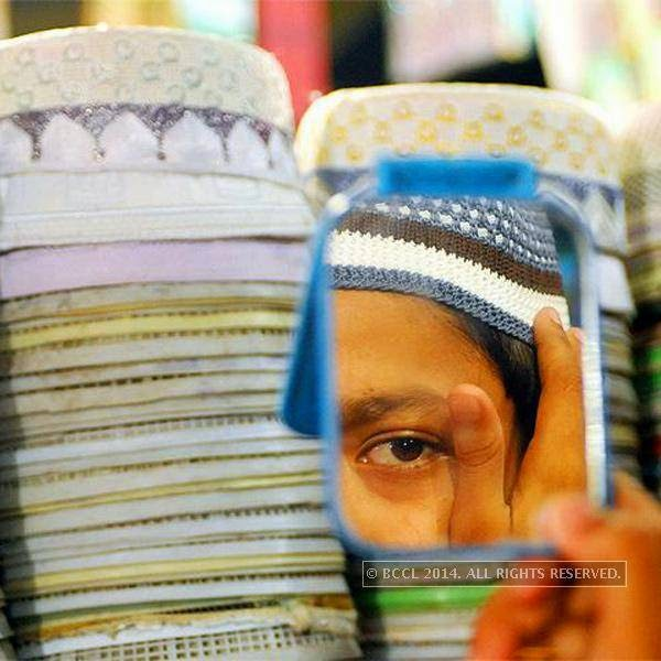 A boy chooses a topi (hat) during the Eid-al-Fitr.