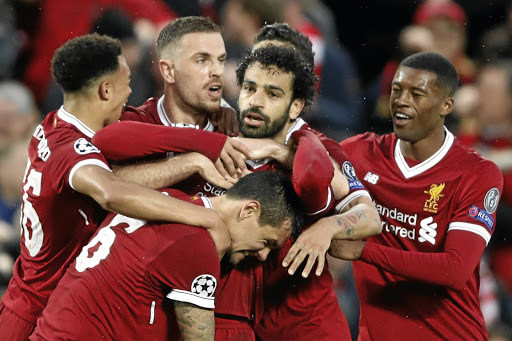 Making the right moves: Mohamed Salah, centre, is mobbed by Liverpool teammates after scoring his second goal against Roma. Picture: REUTERS
