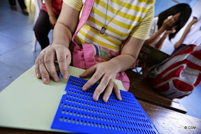 Hands of a child learning Braille