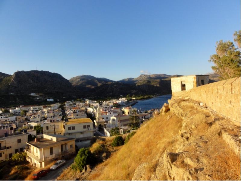 En lav mur med brystvern på toppen av en bratt bakke. Byen Paleochora ligger under høyden.