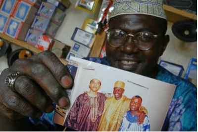 MALIK HOLDING A PHOTO HE TOOK WITH BARACK OBAMA IN HIS SHOP IN KENYA (2004)