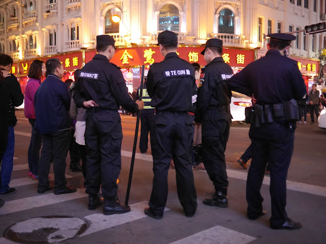 Police in Xiamen, China — one holding a long black rod
