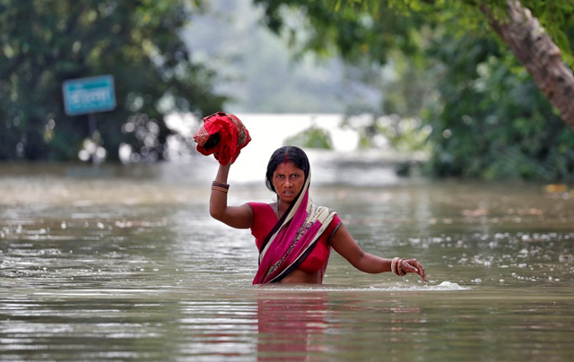 A woman wades through waist-deep floodwaters in India, 25 August 2017. Photo: Cathal McNaughton / Reuters
