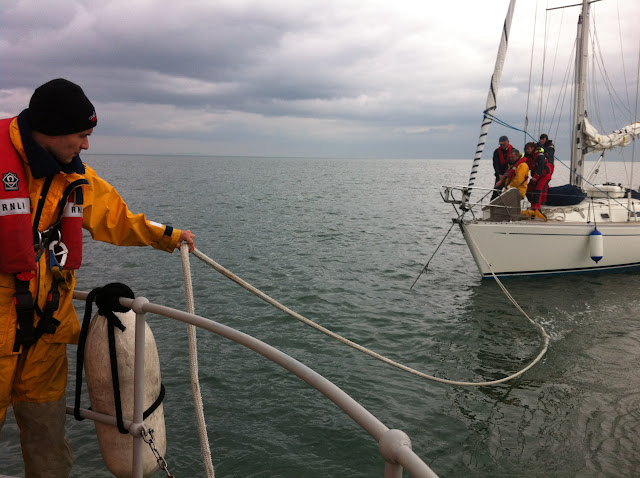 8 April 2012: Feeding out the astern tow rope from the Tyne class lifeboat while crew members aboard yacht pull up their anchor. Photo: RNLI Poole Dave Riley