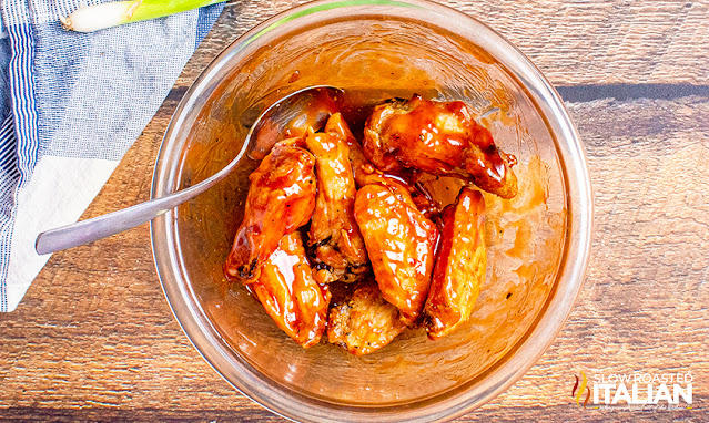 air fryer wings tossed in sauce in a bowl