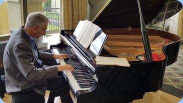 Claude Moffat playing the Village's Kawai grand piano.
