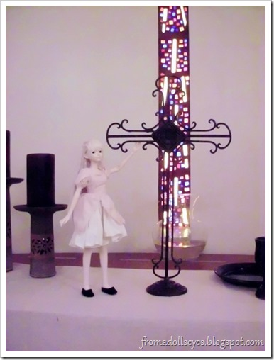 A ball jointed doll standing next to a cross