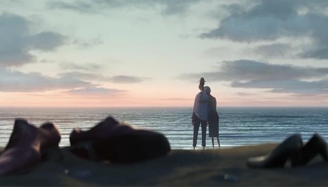 Uma praia no por do sol. Em primeiro plano vemos dois pares de calçados na areia, um masculino e um feminino, são sapatos sociais os dois. E ao fundo na beira do mar tem a figura de duas pessoas negras olhando o horizente, um homem e uma mulher mais velha que abraça o homem.
