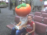 Zachary at CKS Airport sitting by a big tomato head advertisement
