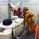 8 April 2012: Crew Member Rich Skerman going aboard yacht to attach a bridle and tow rope. Photo: RNLI Poole Dave Riley