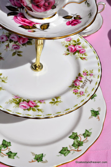 pink and green three-tiered vintage cake stand with teacup top