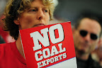 A woman holds a no coal exports sign during the Longview Coal Exports Hearing.