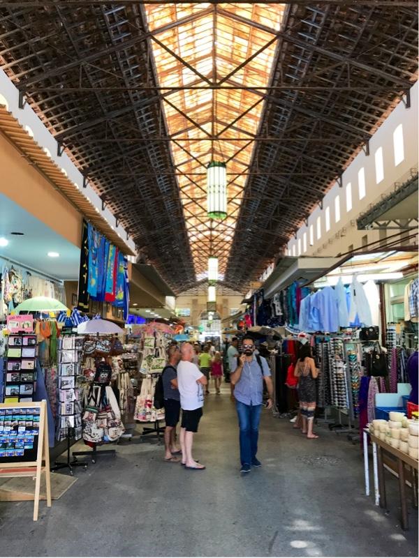 En lang hall med butikker på begge sider av midtgangen. En lang stripe med glass i taket som slipper inn lys.