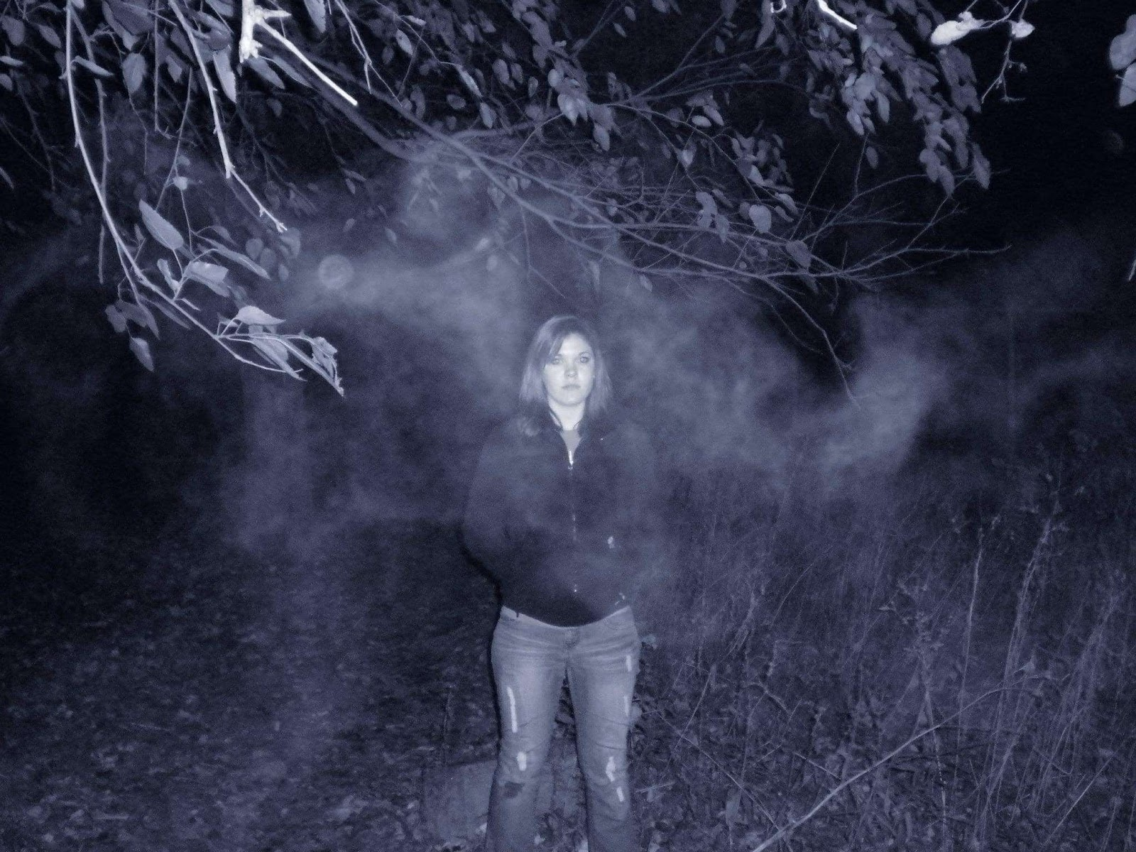 Facebook July 11, 2019 Kenneth Deheve  A few years ago, my friends and I visited one the most haunted places in the country, Bachelors Grove, and we took a photo of one of our friends, Heather Robson, standing under a tree. When we looked back at the photo, there was a suddenly a strange fog that appeared that was not there when we took the photo. We played with the contrast a little bit in the second photo. Still have no idea where it came from but this fucked us up good.