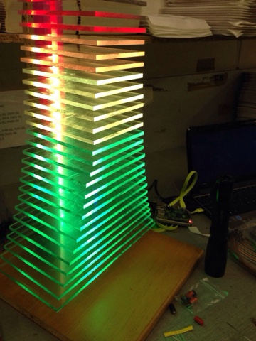 A tapering tower of perspex plates illuminated by LEDs ranging from green at the bottom to red at the top.