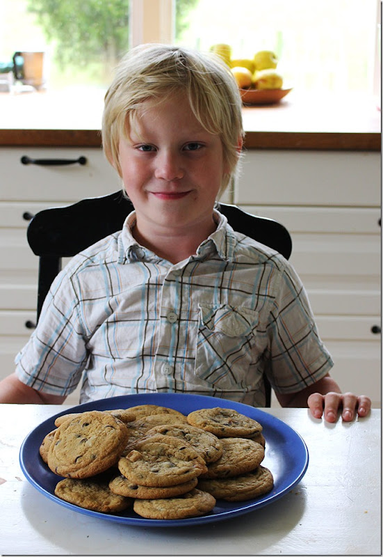 Min son Sebastian sittandes i köket med ett stort blått fat med kakor framför sig.
