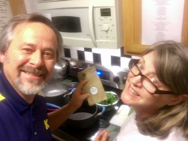 Man in blue shirt with woman wearing glasses in grey shirt cooking in kitchen with black and white wall tiles