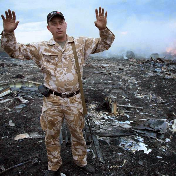 A man gestures at a crash site of a passenger plane near the village of Grabovo, Ukraine, Thursday, July 17, 2014.