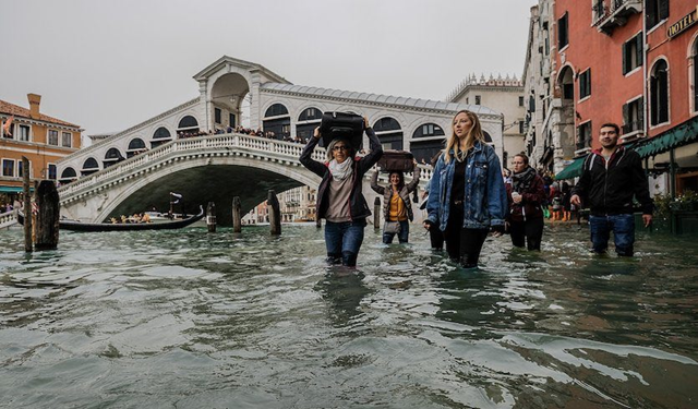Tourists make their way along water-covered sidewalks near the famed Rialto Bridge in Venice, Italy, on Monday, 29 October 2018. High water levels forced schools and hospitals to close, and authorities advised citizens against leaving their homes. Photo: Stefano Mazzola / Awakening / Getty Images