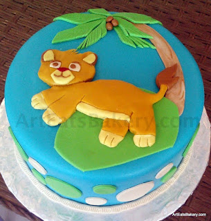 Little Lion King custom creative blue, green, tan and gold baby shower cake with palm tree and coconut