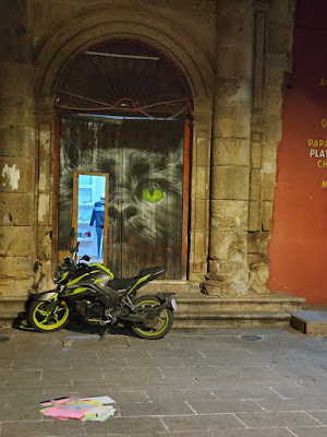 a night shot of a motorcycle parked in front of a shoe shop with an open door with a large face of a black cat painted around it. there are a pile of papers in the foreground.