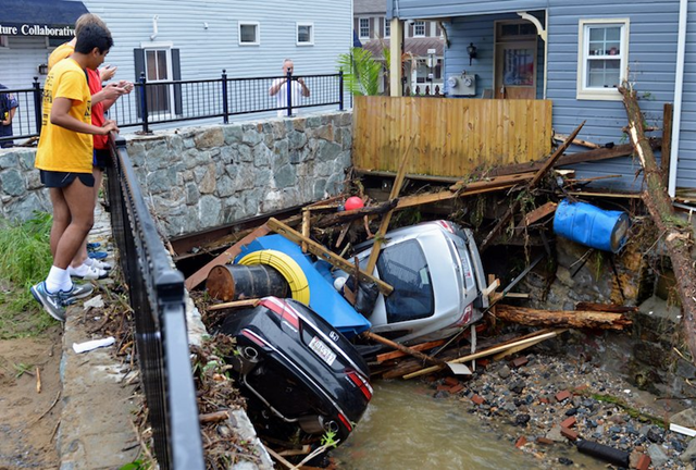 Residents gather by a bridge on Monday, 28 May 2018, to look at cars left crumpled in one of the tributaries of the Patapsco River that burst its banks as it channeled through historic Main Street in Ellicott City, Maryland, on Sunday, 27 May 2018. Photo: David McFadden / AP Photo