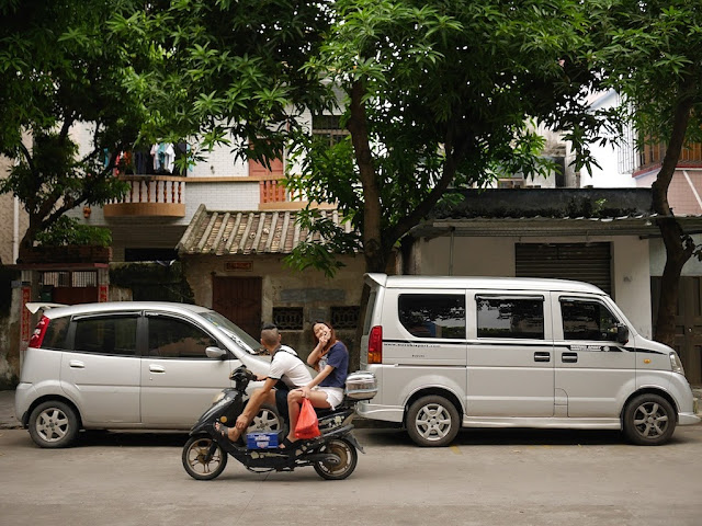 young man looking in the opposite direction while a young woman poses — both on the same scooter