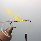 1. Do haczyka o przedłużonym trzonku przywiązuję kolejno: Ogonek z kilku promieni sterówki bażanta, złotą lametę, w 2/3 długości tułowia żółto barwione piórko szyjne koguta.