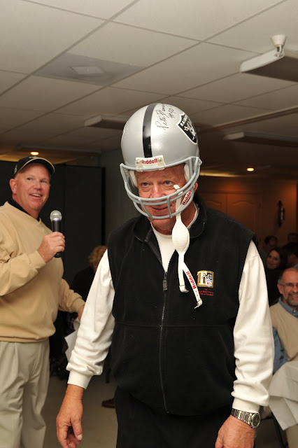Tony Troehler, auctioneer (background) and Pete Banaszak wearing his own autographed helmet which didn't quite fit anymore!
