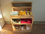 Montessori is all about fostering independence. This beautiful snack hutch presents all the materials our toddlers need to set up their own snack: place mats showing where dishes go, napkins, plates, glasses and, of course, snack food. Notice that there are also clean-up materials to complete the snack cycle!