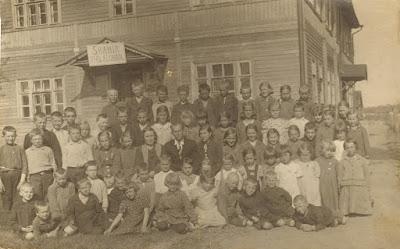 Школьники на фоне школы, в центре учитель Оберпал. Рядом сидят учительницы слева П. Алексеева и справа учительница эстонского.Первый ряд на земле, третий слева Михаил Любомудров, второй ряд 7-ая справа Параскева Львова