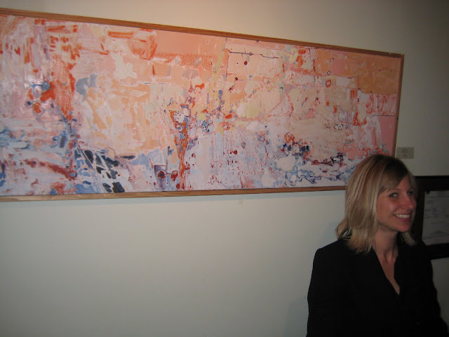 Shea Slemmer (artist and owner of Flux Gallery) at the front desk. In the background is a Christina Foard painting.