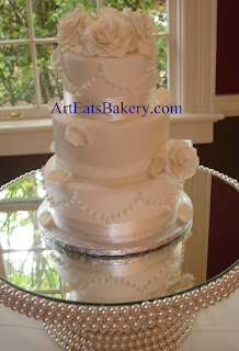 Three tier custom unique ivory fondant wedding cake with handmade sugar roses,petals, pearls, satin and lace ribbon