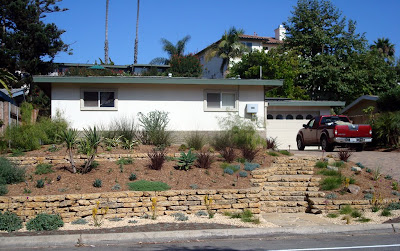 We reused the concrete from the driveway to construct two retaining walls and a stairway.New drought tolerant plantings will anchor the house to the landscape and provide year round low maintenance interest. (two months after installation)