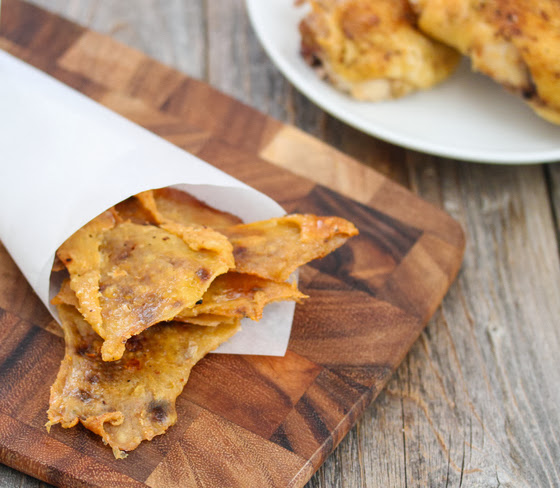chicken cracklings in a paper cone on a cutting board