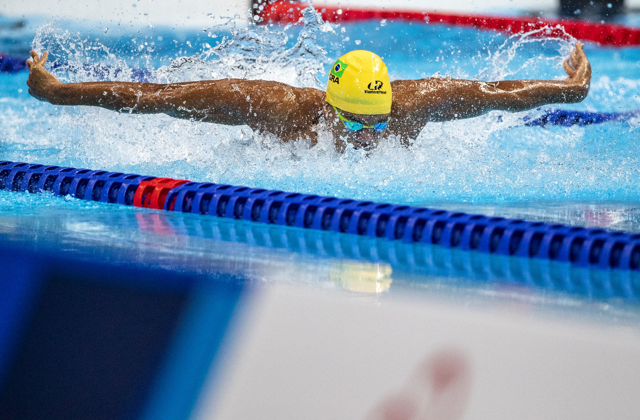 Usando uma touca amarela, Wendell Belarmino faz o nado borboleta com os dois braços para fora da água