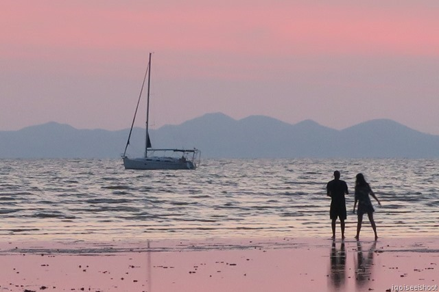 Boat and couple bathed in pink colours of twilight as seen from Nopparat Thara Beach