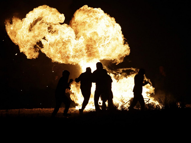 Fire burns at night in the refugee camp in Calais, France, known as 'the Jungle', 26 October 2016. Photo: AP