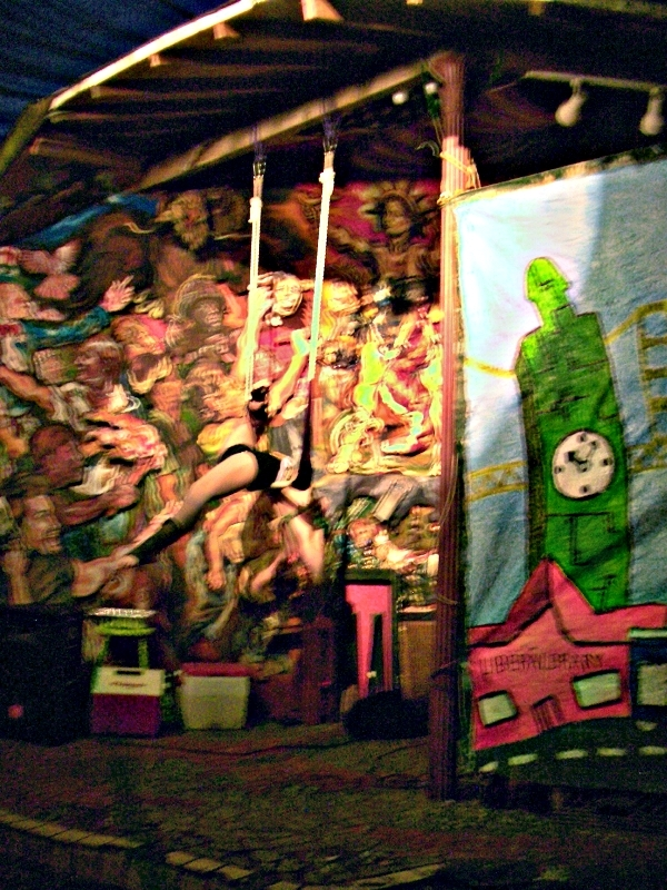 A trapeze artist wearing green lingerie hangs upside down on a trapeze. One of her legs is extended upwards towards the rope and the other is extended in front of her and across the trapeze. In the background, there are multicolored murals and set pieces for the carnival.