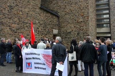 Mahnwache mit roten Fahnen und Transparent: »Faschismus ist keine Meinung, sondern ein Verbrechen!«.