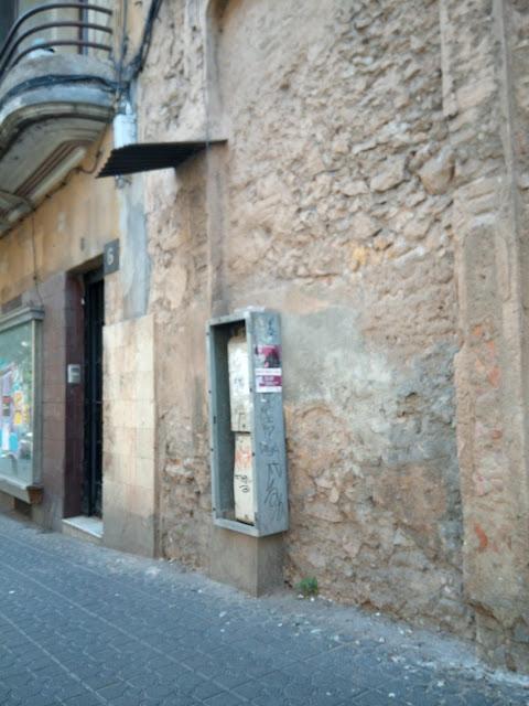 Un armari sense tapa a la vorera del carrer Gasòmetre amb uns tauladeta totalment desplaçada a l'esquerra.