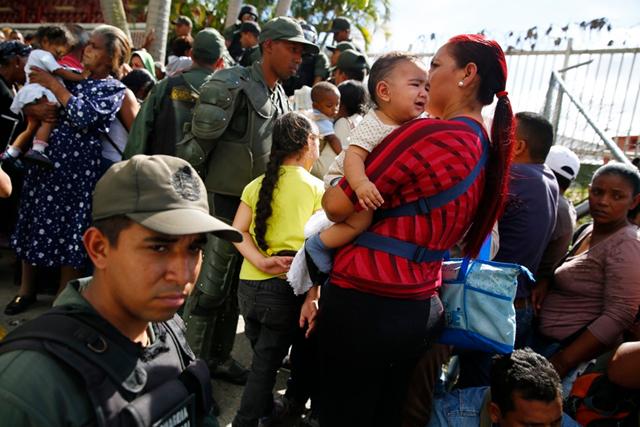 Venezuelan national guardsmen monitor a crowd at a state-run grocery store in Caracas. Photo: Jorge Silva / Reuters