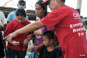 A man with red t-shirt 'CBM Emergency Response Team' pointing to something for a woman and young child
