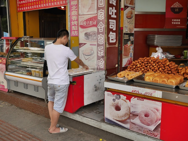 man playing a game of xiangqi alone next to a donuts & bread stand