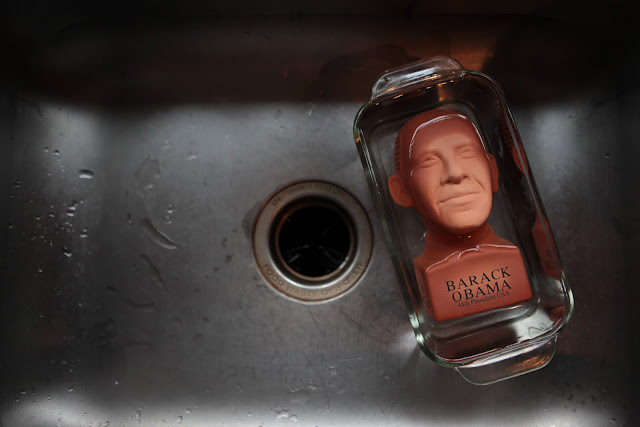 A President Obama Chia Pet soaking in water to get ready for the seeds in a kitchen sink.