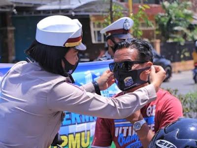 Operasi Yustisi, Polwan Polres Madiun sedang memasangkan masker ke warga.