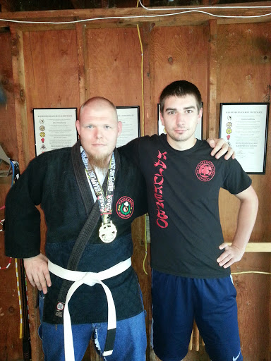 "Matt Jacknewitz, June 2014 NAGA Super Heavyweight gold medal (left, white belt) with John Glendening (right, t-shirt), October 2011 ""Nemesis"" K-1 kickboxing champion"